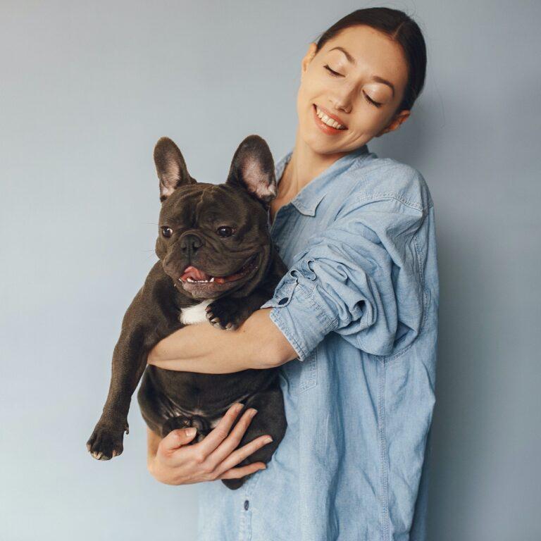 Dog owner holding french bull dog